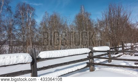 Thick Layers Of Snow Lie On The Unpainted Wooden Fence. There Are Snowdrifts On The Ground. Winter B