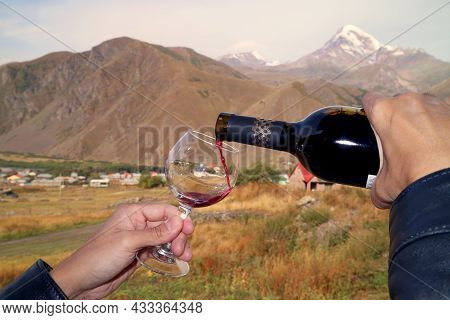 Hand Pouring Red Wine Into Wineglass With Blurry Mt. Kazbek In The Backdrop, Goergia