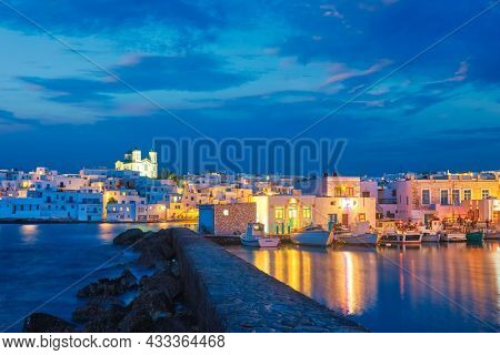 Picturesque view of Naousa town in famous tourist attraction Paros island, Greece with traditional whitewashed houses illuminated in twilight