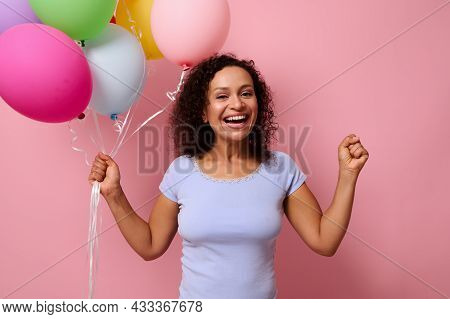 Cheerful Happy African American Woman Rejoices Holding Colorful Air Balloons In Her Hand And Clenchi