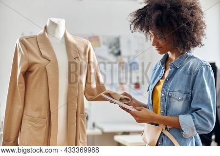 Professional African-american Fashion Designer With Notebook Checks Sleeve Of New Jacket In Workshop