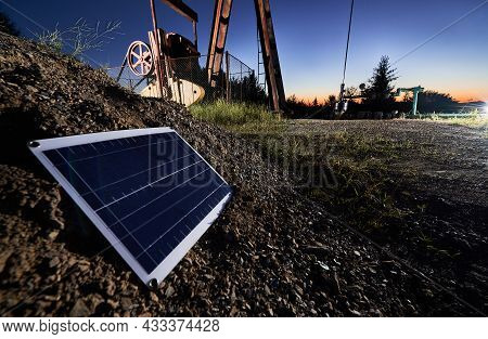Close Up View Of One Small Solar Panel, Which Located On Stone Mound. The Lower Part Of Oil Well On