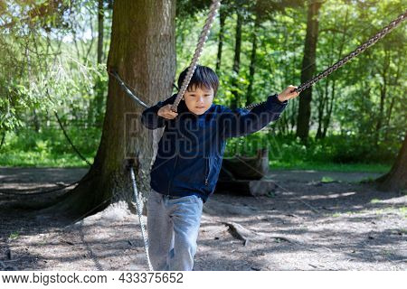 Active Kid Holding Metal Chains In Playground, Child Enjoying Outdoors Activity In A Climbing Rope C