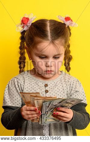 A Beautiful Girl Is Surprised By So Much Money, A Child And Big Money.