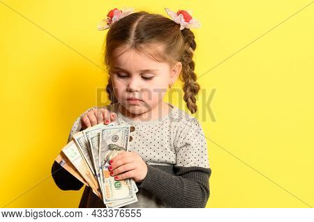 Cute Little Girl On A Yellow Background Background Holds The World's Currency, Financial Literacy An