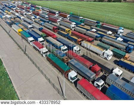 Trucks In Line In The Parking Lot To The Terminal In The Port. Aerial View Of A Large Parking Lot Wi