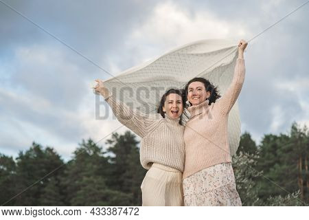 The Two Happiest Women Enjoy Life And Look Into The Distance. Girls In Light Sweaters With A Large K