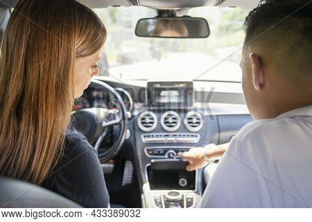 A Red-haired Girl And Her Male Passenger Are Sitting In The Car, Rear View. A Man Is A Car Seller Or
