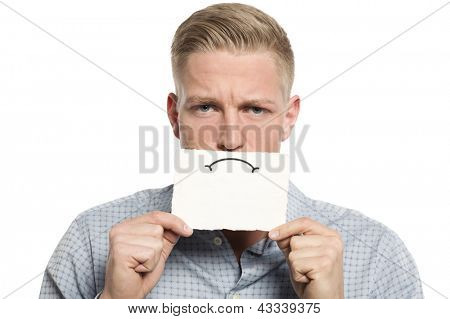 Unhappy young businessman holding empty white card with space for text in front of his mouth isolated on white background.