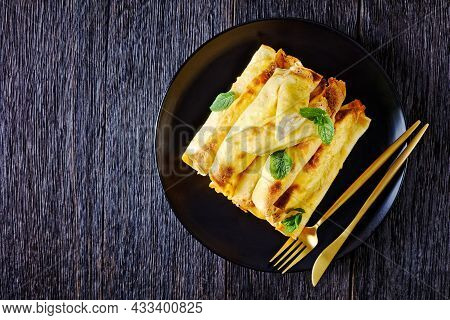 Blintz, Rolled Filled With Sweetened Cottage Cheese Pancakes Or Crepes On A Plate On A Wooden Table,