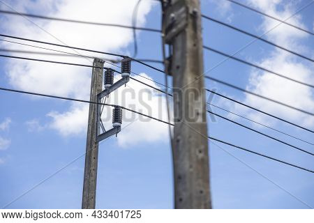 Electric Pole And Power Line On A Clear Day With Blue Sky And White Clouds In The Background