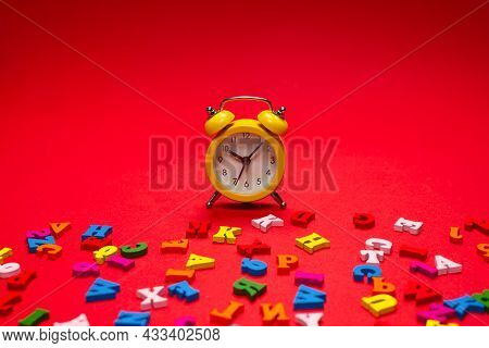 Random Colorful Alphabet And Yellow Alarm Clock On A Red Background, Colorful Letters. Time To Schoo