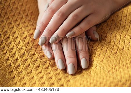 Matt Nude Beige Nails Close Up. Winter Or Autumn Manicure, Woman Hand On Warm Yellow Sweater