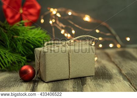 A Christmas Gift Wrapped In Eco Paper. Eco-friendly Gift Wrapping In Kraft Paper. Festive Background
