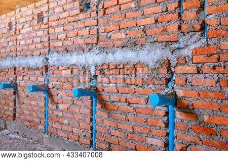Water Supply Pipe Layout Work. Chrome Pipes And Fittings On Brick Wall Background. Piping With Many