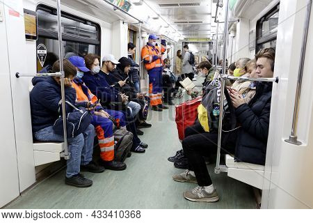 Moscow, Russia - September 2021: Crowd Of People In A Metro Train, Passengers In Masks Sits With Sma