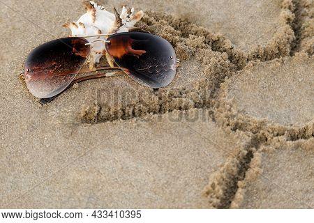 Brown Sunglasses, Seashell, Drawing Sun On Sand тропическом песчаном пляже Close-up With Copy Space.
