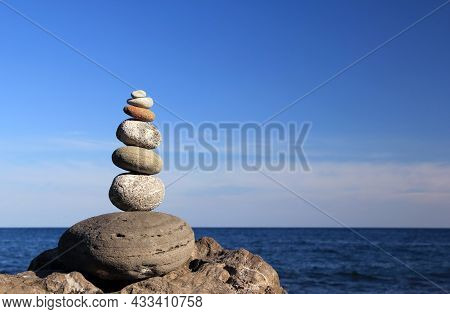 Zen Stones. Zen Stone Pyramid Illuminated By The Rays Of The Evening Sun Against The Background Of T