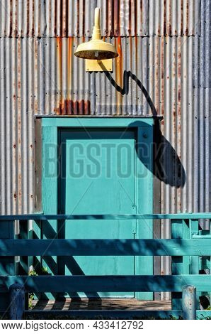 Colorful door and light fixture in on rusty building with corrugated metal siding