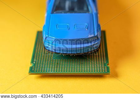 Close Up View Of A Blue Toy Car On Top Of A Microprocessor.