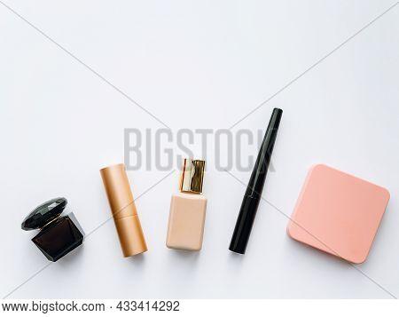 Flatley: Perfume, Lipstick, Foundation, Eyeliner And Blush On A Light Background, Copy Space
