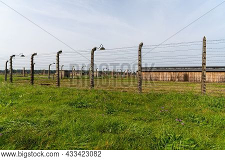 Barbed Wire Fences Surround Prisoner Barracks In The Auschwitz Concentration Camp