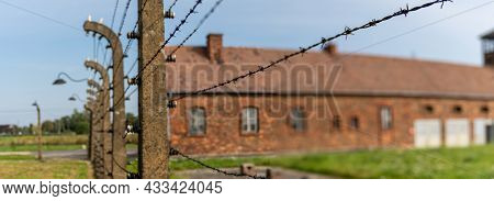Selective Focus Of Barbed Wire Fence With The Auschwitz Concentration Camp Gatehouse In The Backgrou