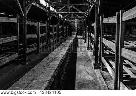Black And White View Of View Of The Interior Of One Of The Wooden Prisoner Barracks In The Auschwitz