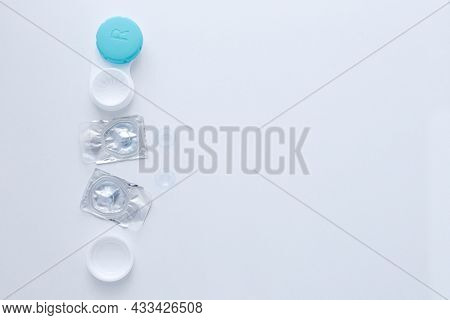 A Container For Lenses, Two Sealed Lenses And Lenses Lying On A Table On The Side On A White Backgro