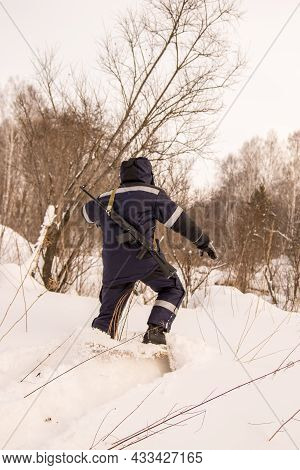 A Hunter Or Forester With A Weapon On His Shoulders On Wide Forest Skis Walks Through Deep And Loose