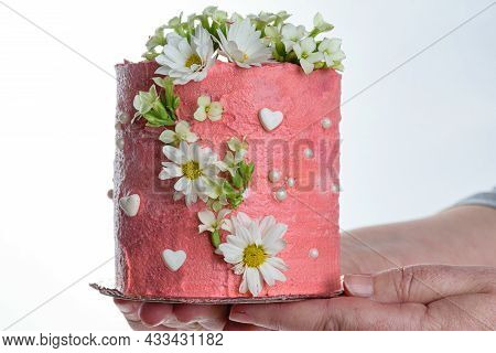 Confectioner Holding A Chocolate Cake Covered With Pink Butter Cream. Decorated With White Hearts, P