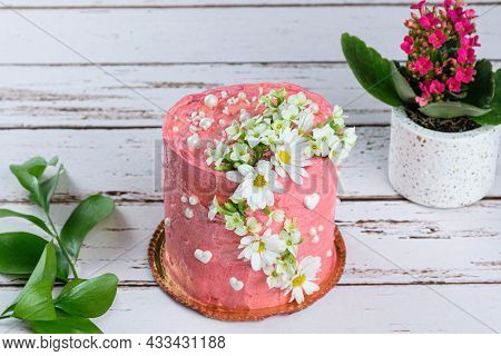 Chocolate Cake Covered With Pink Butter Cream. Decorated With White Hearts, Pearls And Flowers.