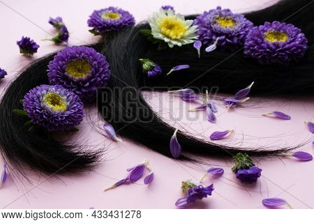 Dark Hair With Lilac Flowers And Petals On It. Hair Care Concept.