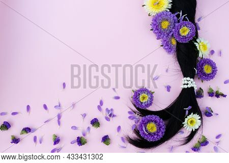 Pigtail From Dark Hair With Fresh Flowers In It. Hair Care Concept.