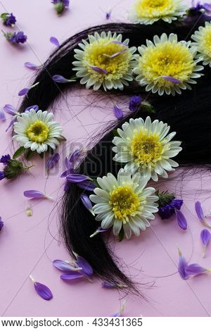 Dark Hair With Yellow Flowers And Petals On It. Hair Care Concept.