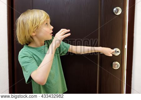 Little Boy Alone At Home. Child Is Opening The Door To Someone. Baby Is Opened Door To A Stranger An