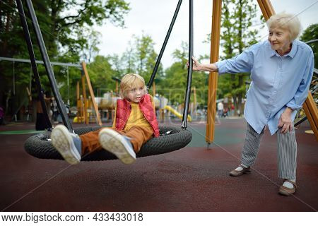 Gray-haired Elderly Lady Shaking His Grandchild On Swing At Playground In Park. Friendship Of Grandm