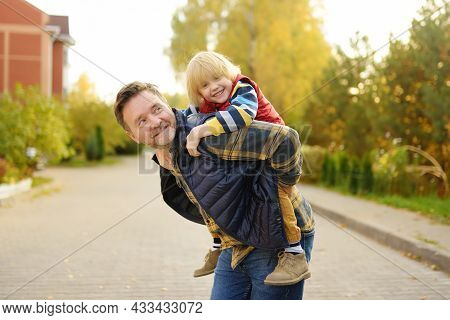 Little Boy And His Father Having Fun During Stroll On Sunny Autumn Day. The Father Rides The Child O
