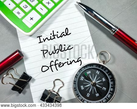 Business Concept.text Initial Public Offering Writing On Notepaper With Paper Clips,pen,compass And