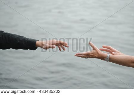 Man And Woman Hands Reaching Out Each Other, Holding Hands Over Grey Monochrome Water. Relations, Re