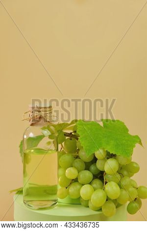 Grape Seed Oil.bottle And Green Grapes On Podium On A Beige Background. Organic Natural Bio Grape Se