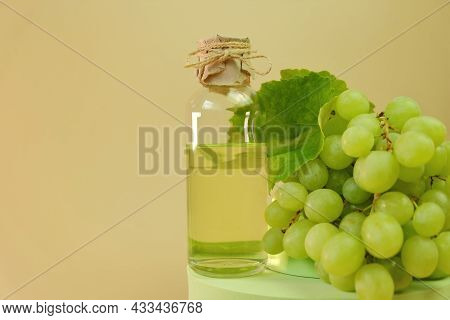 Grape Seed Oil.bottle And Bunch Of Green Grapes On A Beige Background. Organic Natural Grape Seed Oi