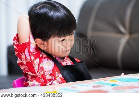 Cute Child Is Reaching For Her Back Scratching Her Back Due To Itching From A Label Attached To Her