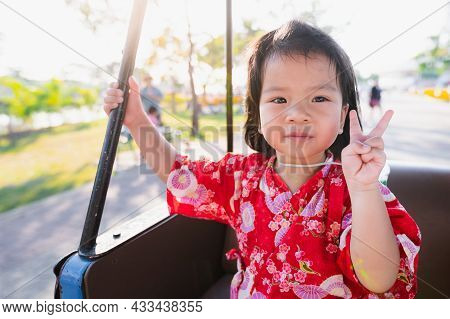 Happy Girl Is Riding In A Golf Cart In The Park During Spring. Sweet Smile Baby Raises Two Fingers.