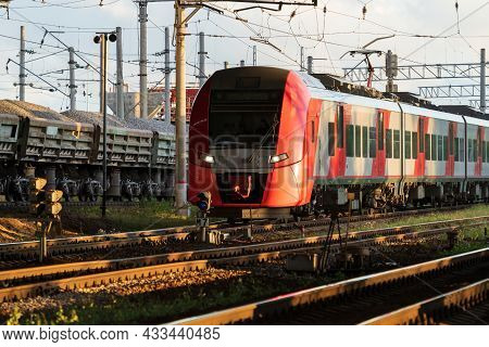 Modern Russian Intercity High Speed Train At Sunset. Industrial Landscape With Passenger Train On Ra