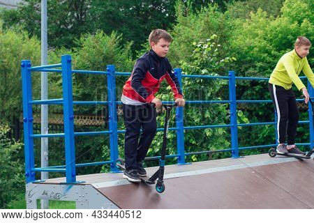 Novokuznetsk, Russia - July 19, 2021: Group Of Boys Ride A Scooter In An Extreme Park. Study Of Extr