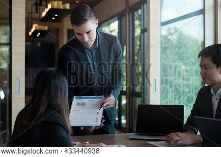 During A Business Meeting With Colleagues, A Company Marketologist Gives A Presentation About Market