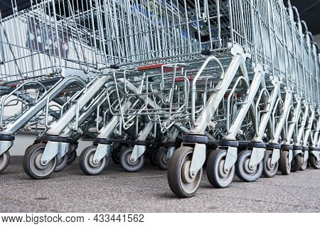 Many Empty Shopping Carts On The Shop Parking. Row Of Shopping Trolleys For Supermarket Buyers