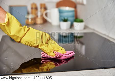Cleaning Induction Stove. Woman In Yellow Rubber Gloves Cleans Kitchen Induction Hob With Cleaning S
