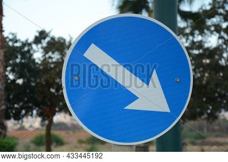 Pass Designated Place On Right. Blue Road Sign Pass On This Side With White Arrow Pointing To The Ri